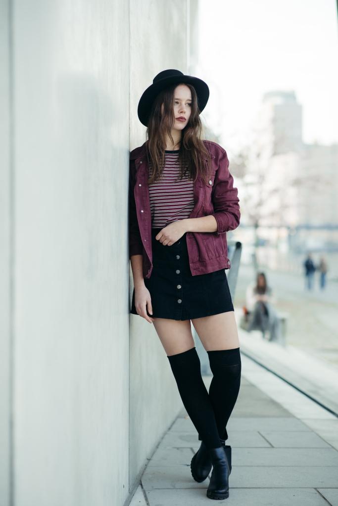 Rock mit Knopfleiste schwarz, buntes Streifenshirt, Overknee-Strümpfe + Hut